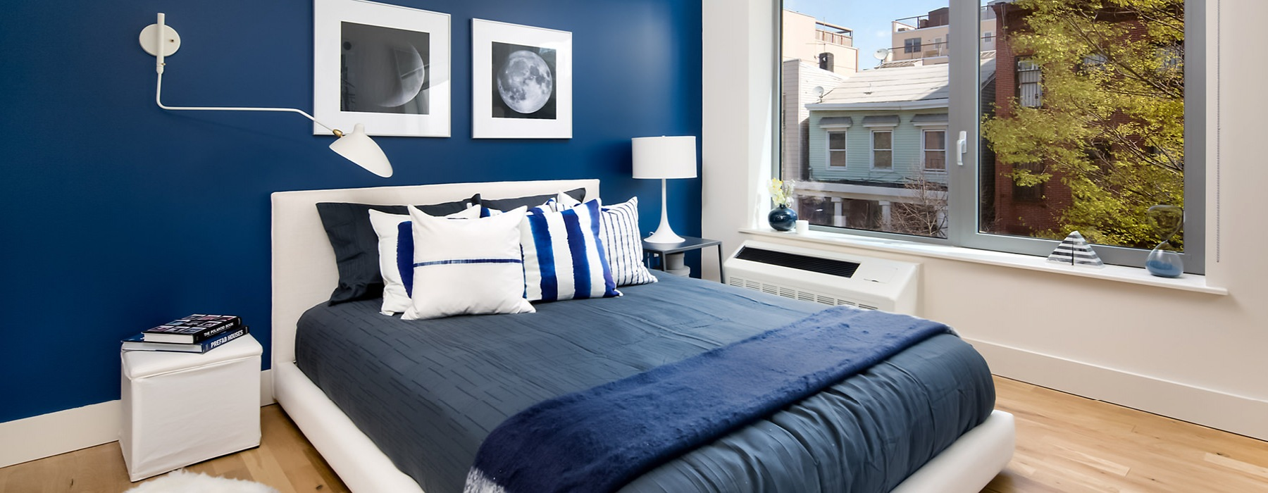 Bedroom with large open window, blue comfort set and blue accent wall